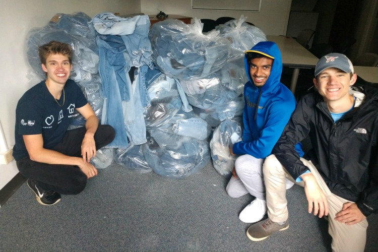 Erek, Siddath Marapane, and Maddox Linneman with the total amount of jeans collected that day.