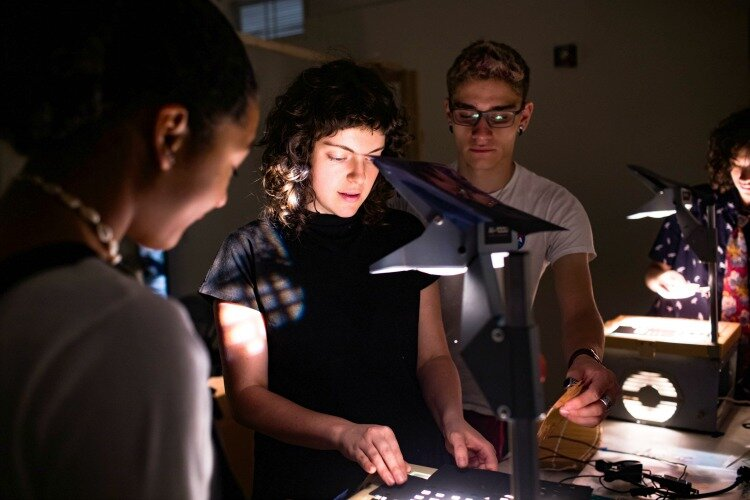 Lizzy DuQuette, ArtWorks teaching artist, demonstrates shadow puppetry to her youth apprentice team. DuQuette worked with four apprentices to create a shadow puppet play to be performed at BLINK.
