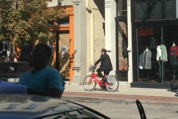 Mayor John Cranley rides a Red Bike on the sidewalk