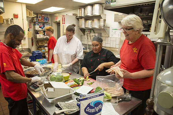 Sister Judy Tensing (right) works with staff and trainees in the Venice on Vine kitchen