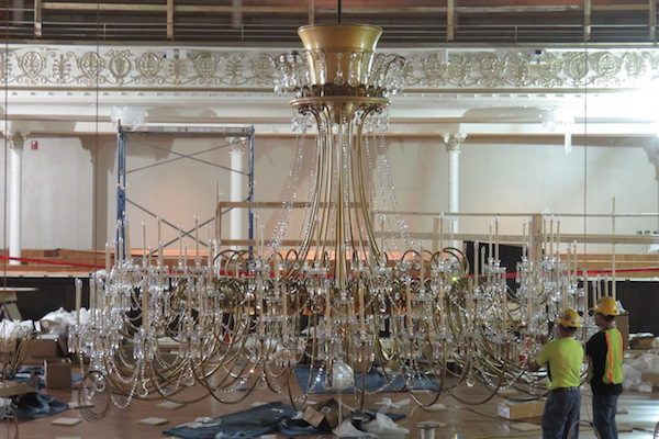 Workers reinstall a crystal chandelier following Springer Auditorium restoration.