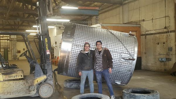 Paul and Josh Kemp stand in front of the first tank at their family's brewery.