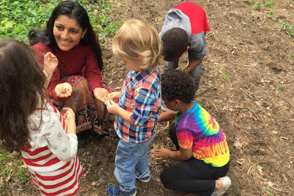 Heärt Montessori co-founder Nayana Shah shows children a handful of seeds while exploring the outdoors.