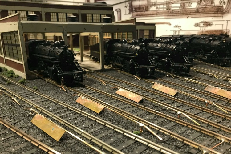 Little locomotives wait on tracks in their own small station.