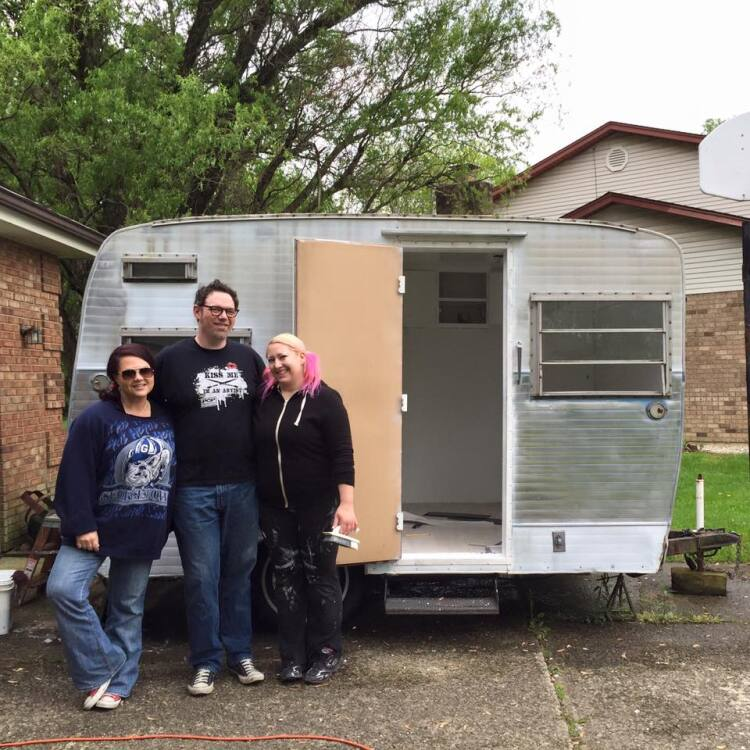 Janet Creekmore, Ben Jason Nel and Melissa Mitchell with their vintage camping trailer before it became a mobile art gallery.