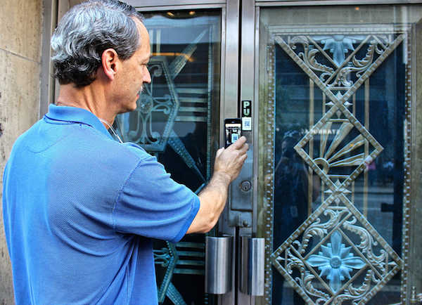 Architectural photographer J. Miles Wolf demonstrates the QR code on one of his architectural detail photographs, installed along a downtown walking route.