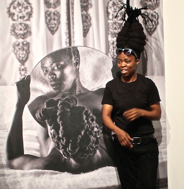 "Artist and activist Zanele Muholi poses next to one of her self-portraits in the series Somnyama Ngonyama (""Hail the dark lioness""), which takes up a subset of the Personae exhibition at the Freedom Center."