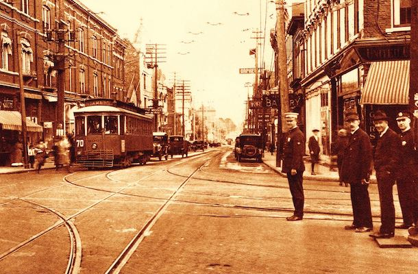 1910s-1920s-era photo shows a bustling streetcar stop and Peeble's Corner commercial district.