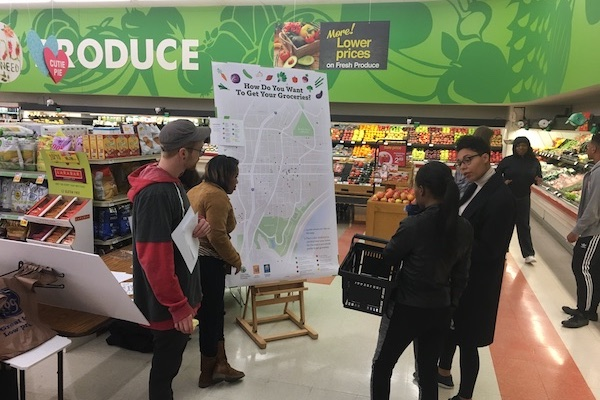 Walnut Hills residents discuss a graphic showing neighborhood food resources installed by WHRF at soon-to-close Kroger location.