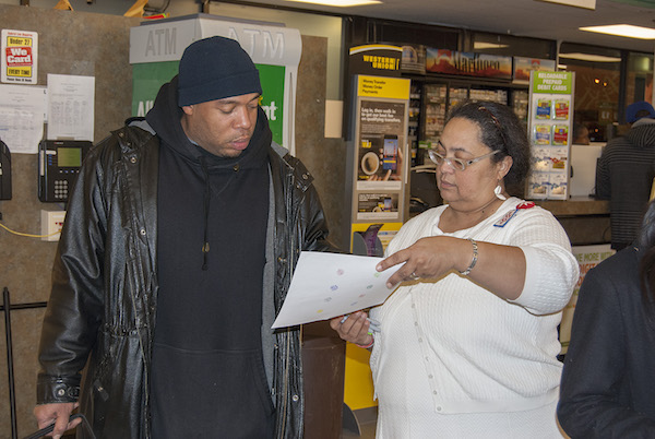 Walnut Hills resident and community leader Kathryne Gardette discusses food-sourcing options with Kroger shoppers.