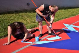 Sam and Thad Becker fill in one of the six colors at George Stone court.