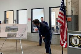 Kentucky Gov. Andy Beshear looks at plans for Wilder's redevelopment during his announcement of a grant for the project.