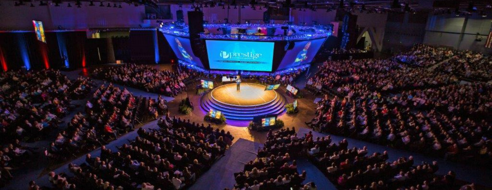 "Prestige AV & Creative Services supports corporate meetings of all sizes including this ""in the round"" multi-screen set for 4,000 attendees. <span class='image-credits'></span>"